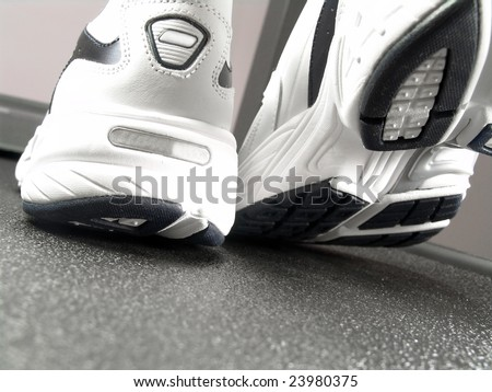 Closeup view of brand new sport shoes running walking on a treadmill (low angle perspective) - stock photo