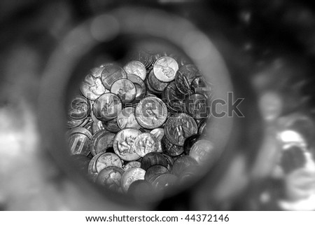 Closeup view of change in a plastic bottle, in black and white. - stock photo