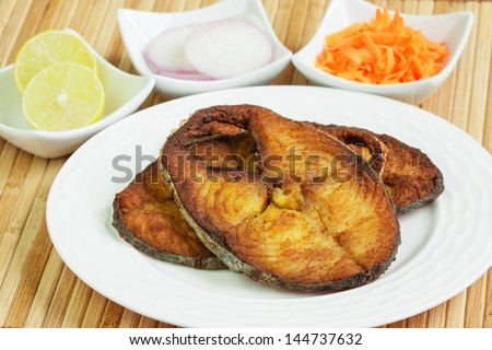 Closeup view of delicious seer/mackerel fish fillets fry served with shredded carrots, raw onion rings, lemon. - stock photo