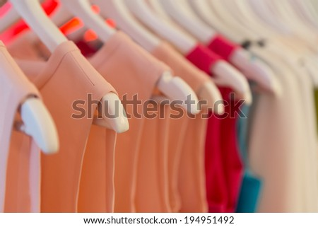 Closeup view of dresses on clothes hangers with very shallow depth of field. - stock photo