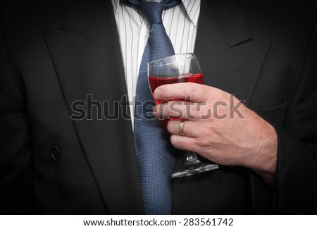 Closeup view of drunk business man in suit and tie holding wine glass.