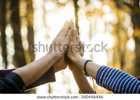 Closeup view of four people joining their hands together high up in the air outside in a forested area. - stock photo