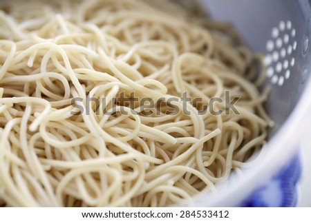 Closeup view of fresh boiled spaghetti pasta inside colander. Shallow depth of field - stock photo