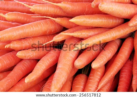 Closeup view of fresh carrot pile on a display at the local farmers market. Suitable for an abstract background. - stock photo