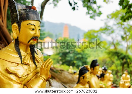 Closeup view of Golden Buddha statue in the Ten Thousand Buddhas Monastery on background of a red pagoda and forest in Hong Kong. Hong Kong is popular tourist destination of Asia. - stock photo