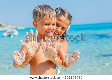 Closeup view of hands by the girl and boy on the sand beach.