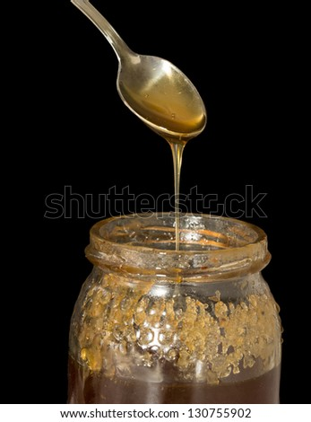 Closeup view of honey over silver spoon and jar, black background - stock photo