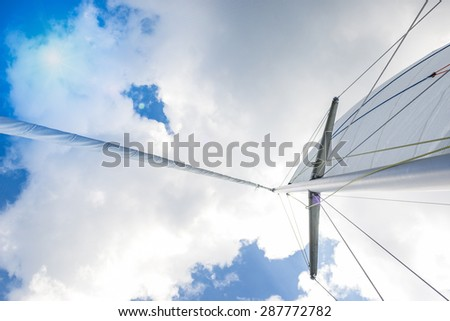 Closeup View of Mid-Size Yacht Mast and Canvas Sail Shot Against Bright Summer Sun. Horizontal Image Orientation - stock photo