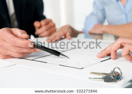 Closeup view of new home keys and house plan during a discussion with a real estate agent - stock photo