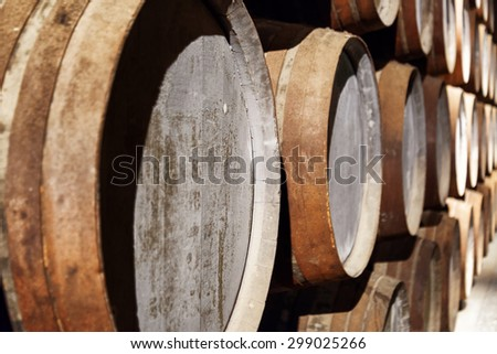 Closeup view of oak barrels stacked in the old cellar with aging Port wine from the vineyards Douro Valley in Portugal. Product of organic farming. - stock photo