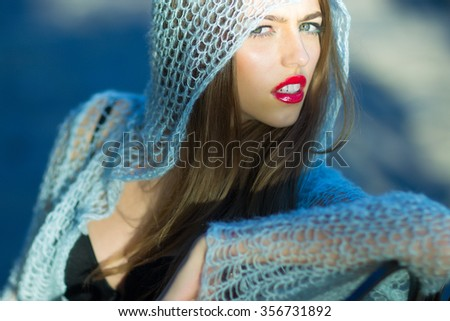 Closeup view of one attractive sexy pensive young stylish enigmatic woman with bright red lip gloss in blue knitted cloth sitting outdoor on blurred background, horizontal photo - stock photo