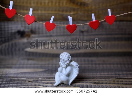 Closeup view of one beautiful cupid angel decorative figurine near red clothes-peg in shape of heart with no people on wooden background, horizontal picture - stock photo