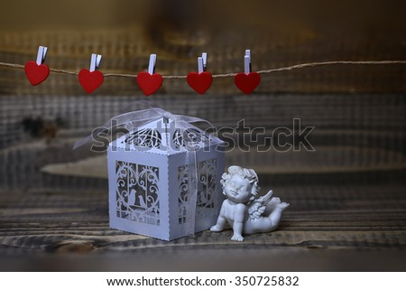 Closeup view of one beautiful cupid angel decorative figurine near white paper greeting valentine box near red clothes-peg in shape of heart with no people on wooden background, horizontal picture - stock photo