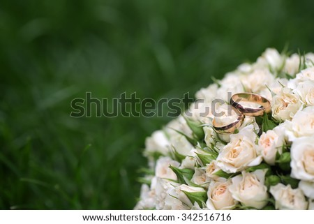Closeup view of one beautiful fresh bright white yellow big wedding bouquet of rose flowers lying on green grass sunny day outdoor on natural background, horizonbtal picture - stock photo