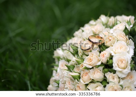 Closeup view of one beautiful fresh bright white yellow big wedding bouquet of rose flowers with gold rings lying on green grass sunny day outdoor on natural background, horizontal picture - stock photo