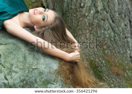 Closeup view of one beautiful sensual sexy young mysterious woman with long lush hair falling down in emeral dress lying on grey stone in forest outdoor on natural background, horizontal picture - stock photo