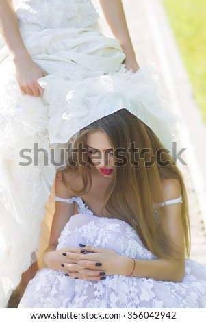 Closeup view of one beautiful sensual stylish sad young model woman in luxury lace dress with diamonds and long lush hair sitting under female skirt sunny day outdoor, vertical picture - stock photo