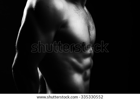 Closeup view of one handsome sexual strong young male bare chest of muscular body standing posing on studio background black and white, horizontal picture