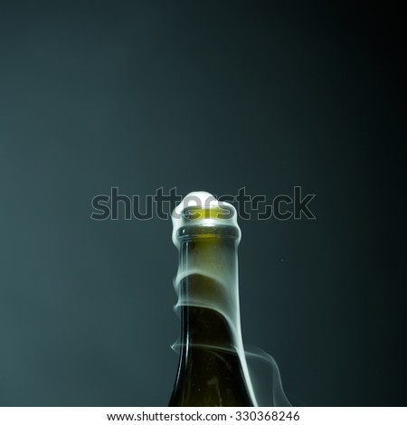 Closeup view of one new open full champagne wive sweet or dry drink green glass bottle with beautiful white smoke for celebration christmas or new year in studio on black background, square picture - stock photo