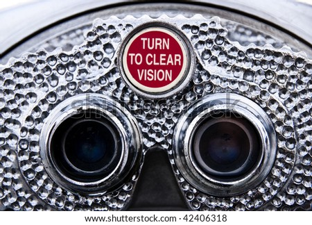 Closeup view of pay binoculars. The red knob reads: Turn to clear vision. - stock photo