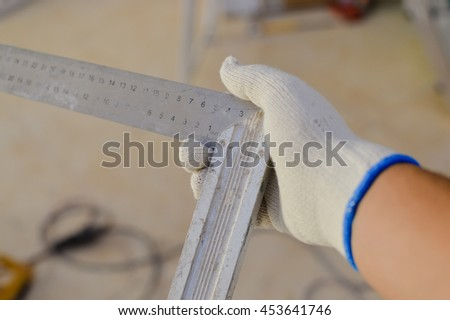 Closeup view of person hand in glove holding measuring ruler tool 90 degrees, construction site background. - stock photo