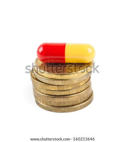 Closeup view of stack of coins and pill over white background - stock photo