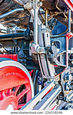 Closeup view of steam locomotive wheels, drives, rods, links and other mechanical details. White, black and red colors. Vertical, portrait orientation photography - stock photo