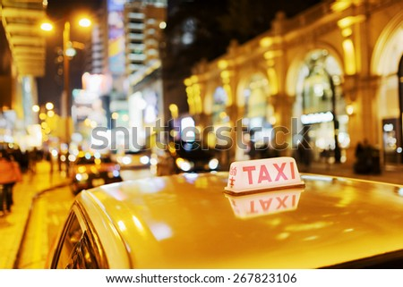 Closeup view of taxi on the street of elite stores at evening in Hong Kong. Hong Kong is popular tourist destination of Asia and leading financial centre of the world. - stock photo