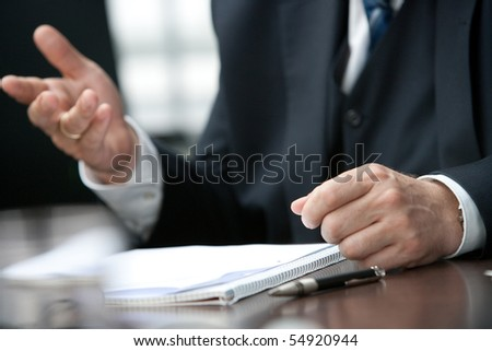 closeup view of the gesticulating hands of a business man sitting on a table - stock photo