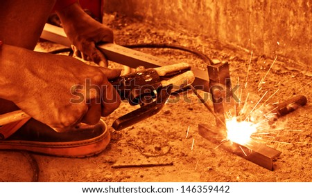 Closeup view of worker welding  two pieces of metal together,vintage  color tone. - stock photo
