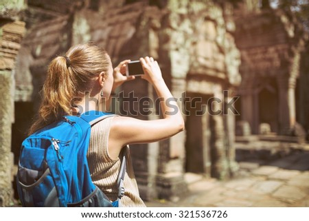 Closeup view of young female tourist with blue backpack and smartphone taking a picture of mysterious ruins in the ancient Preah Khan temple in Angkor. Siem Reap, Cambodia. Toned image. - stock photo