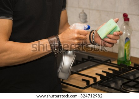 Closeup View of Young Man's Arms Cleaning Surface of Stove Top in Kitchen with Sponge - Responsible Man Doing Housework in First Apartment - stock photo