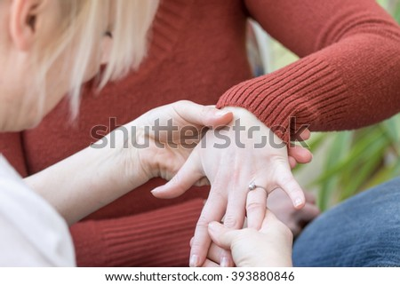 Closeup view of young woman is showing engagement ring on his finger to middle aged blond woman.  - stock photo