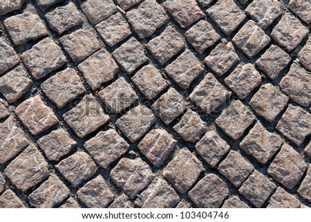Closeup view on a cobblestone road - pattern - background - contrasty due to a side sunlight