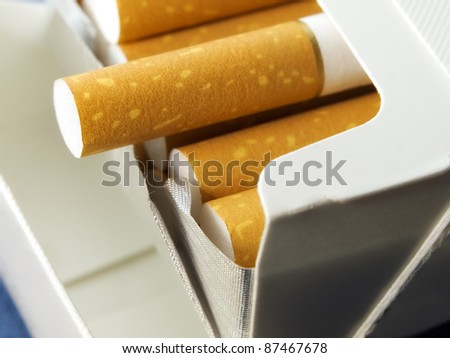 Closeup view on an open pack of cigarettes. - stock photo
