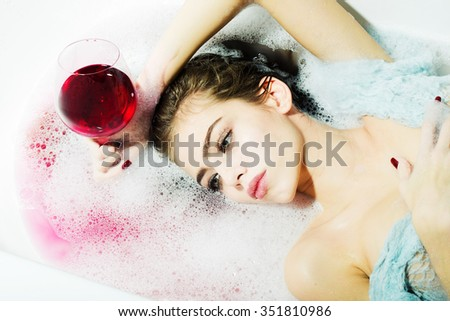 Closeup view portrait of attractive young sexy girl with wet hair lying in white bath tab full of water and soap foam holding drinking glass with red liquid as elixir of beauty or desert wine indoor - stock photo