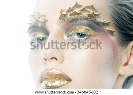 Closeup view portrait of one beautiful wild young woman with bright golden grey and yellow animal makeup with thorns on face in studio, horizontal picture