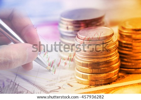 Closeup view : Stack of coins and a hand holding a ballpoint pen is examining a technical chart of financial instrument. An idea / concept of currency trading, making a decision for an optimal gain. - stock photo