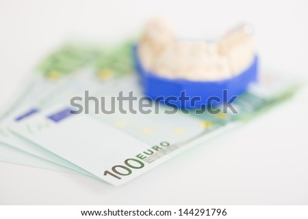 Closeup view with shallow dof of 100 euro notes with a dental implant mould on top of them conceptual of dental expenses, prosthetics and healthcare - stock photo