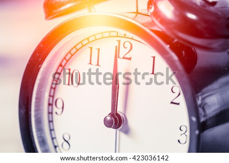 closeup vintage clock selective focus at number 12 o'clock with sun light vintage color tone for postcard. - stock photo