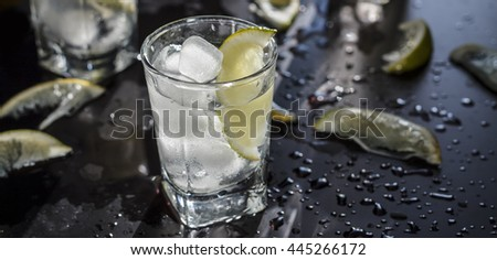 Closeup vodka in a glass with ice, lime vodka, Gin, tonic, tequila - stock photo