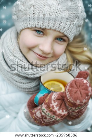 closeup winter portrait of a cute girl with a cup of hot tea outdoors - stock photo