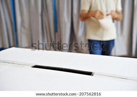 Closeup with a ballot box and a man comming out from the vote cabin in the background - stock photo
