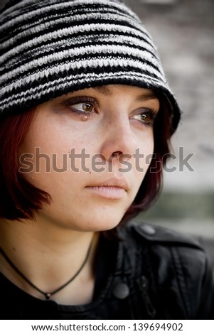Closeup woman face in retro grunge style with tears on her eyes - stock photo
