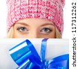 closeup woman face wearing pink hat holding gift box - stock photo