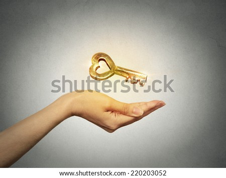 Closeup woman hand holding offering new golden key to success isolated grey wall background. Positive thinking. Successful career, business, opportunity, real estate, good relationship concept - stock photo