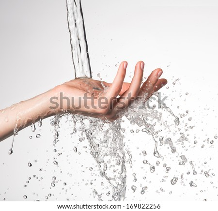 Closeup woman hand under the stream of splashing water - skin care concept