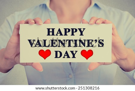 Closeup woman hands holding white card sign with happy valentine's day text message isolated on grey wall office background. Retro instagram style image - stock photo