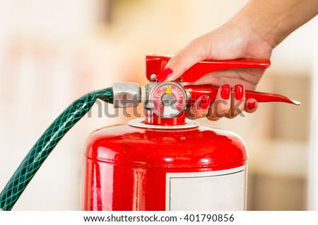 Closeup woman hands with red nailpolish showing how to operate fire extinguisher - stock photo
