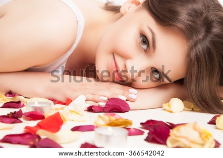 closeup woman on rose petals in white underwear - stock photo